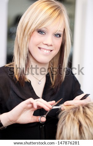 Beautiful smiling young female trainee hairstylist cutting blond hair with scissors in a hair salon - stock photo