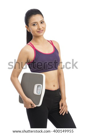 Beautiful smiling young fitness woman in tracksuit holding weigh scale over white background - stock photo