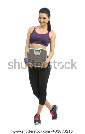 Beautiful smiling young fitness woman in tracksuit holding weighing scale over white background - stock photo