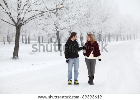 Beautiful smiling young girl and boy in a cold winter day