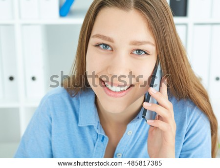 Beautiful smiling young girl talking on the mobile phone in the office.