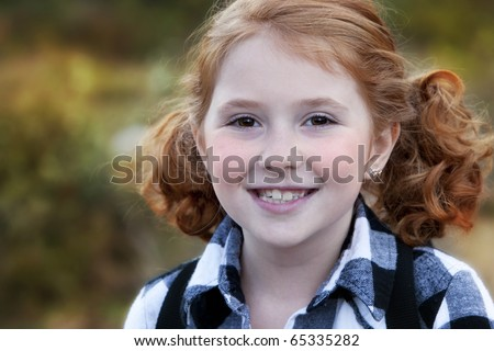 Beautiful smiling young girl with red hair outdoors in Autumn season - stock photo