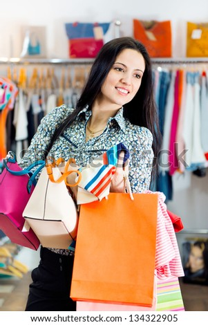 Beautiful smiling young girl with shopping bags in boutique - stock photo