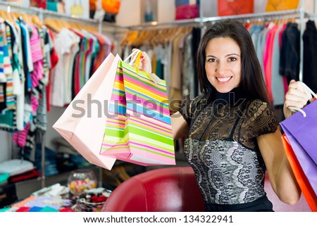 Beautiful smiling young girl with shopping bags in boutique