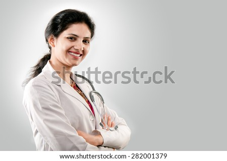 Beautiful smiling young Indian lady doctor with crossed arms and stethoscope in sari over grey background - stock photo
