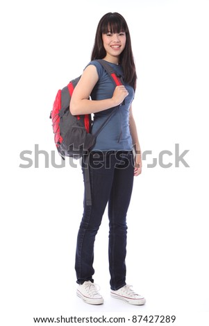 Beautiful smiling young Japanese teenager high school student girl wearing blue denim jeans and t shirt, school backpack over shoulder. - stock photo