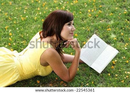 Beautiful smiling young lady reading a book while laying on the grass - stock photo