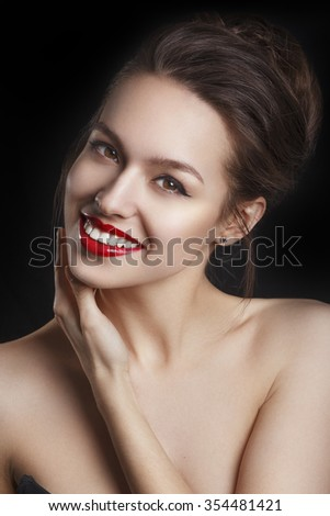 Beautiful smiling young model with red lips and red manicure on black background. Happy model girl  - stock photo