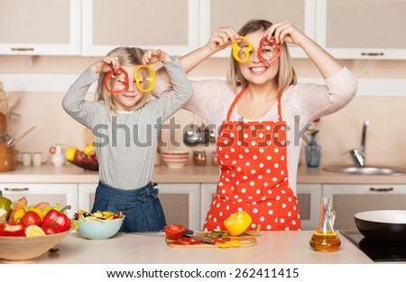 Beautiful smiling young mother and her little daughter having fun while cooking salad. Kitchen interior. Concept for young kitchen hands - stock photo