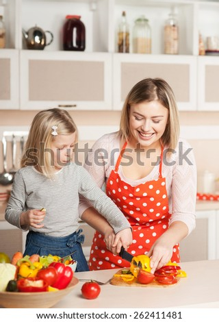 Beautiful smiling young mother helping her little daughter to chop paprika while cooking salad. Kitchen interior. Concept for young kitchen hands - stock photo
