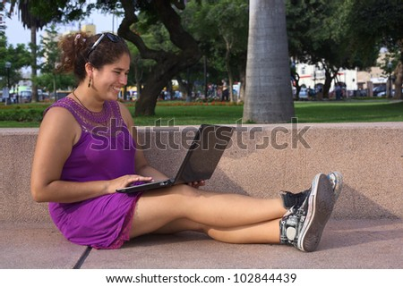 Beautiful smiling young Peruvian woman with laptop computer in a park in Lima, Peru (Selective Focus, Focus on the face of the woman) - stock photo
