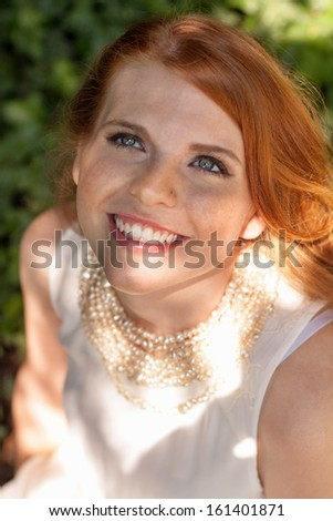 beautiful smiling young redhead woman portrait outdoor in summer