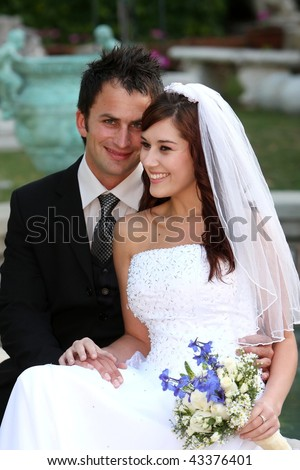 Beautiful smiling young wedding couple sitting together at their garden reception