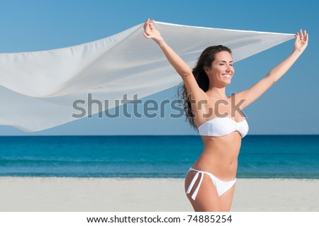Beautiful smiling young woman blowing white cloth in the breeze of a summer day - stock photo