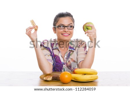 Beautiful smiling young woman choosing between healthy fruits and cakes, over white background. - stock photo