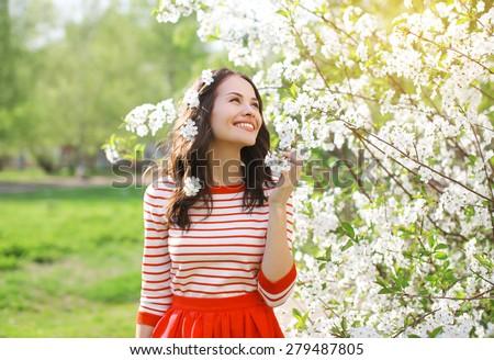 Beautiful smiling young woman enjoying smell flowering spring garden - stock photo