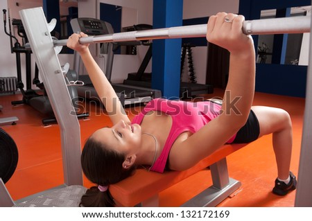 Beautiful smiling young woman exercising with weights in the gym. - stock photo
