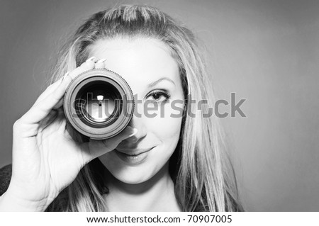 Beautiful smiling young woman holding camera lens like it was spyglass. Black & White - stock photo