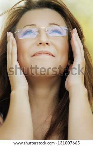 Beautiful smiling young woman holds glasses and looking up, against background of summer green park. - stock photo