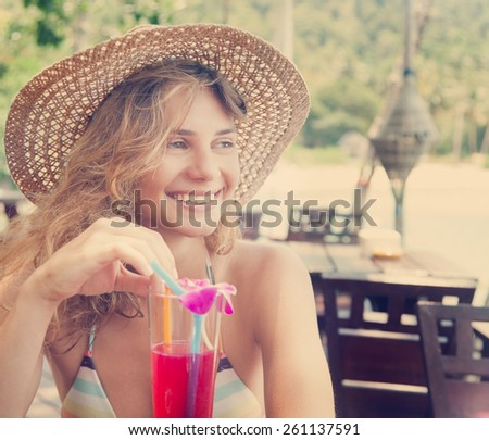 Beautiful smiling young woman in a hat with a cocktail at the beach cafe