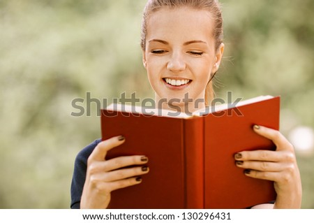 Beautiful smiling young woman in dark blouse reads red book, against green of summer park. - stock photo