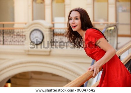 Beautiful smiling young woman in red dress has kept appointment, holds on to banister and looks out for friend in big hall. - stock photo