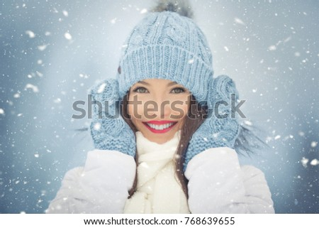 Beautiful smiling young woman in warm clothing. The concept of portrait in winter snowy weather.