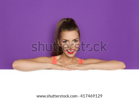 Beautiful smiling young woman lean on white copy space. Head and shoulders studio shot on purple background. - stock photo