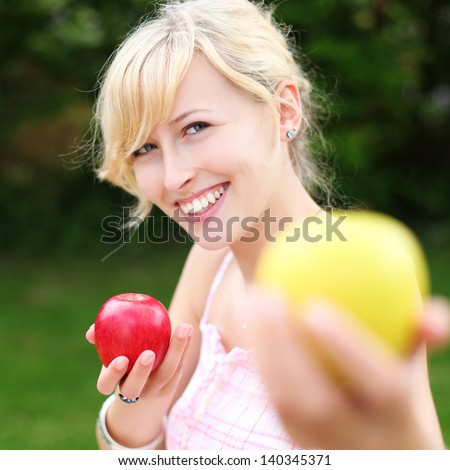 Beautiful smiling young woman offering a yellow apple to the viewer while holding a delicious ripe red one in her other hand, focus to the woman - stock photo