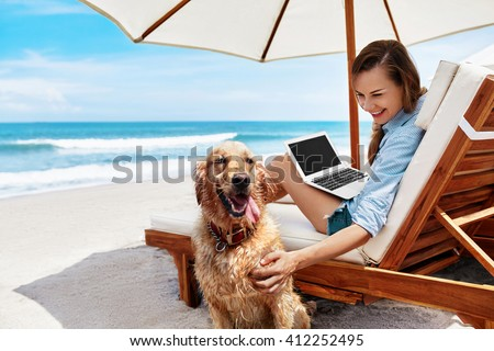 Beautiful Smiling Young Woman Playing With Pet While Using Laptop Computer Outdoors By Sea. Happy Girl Having Fun With Her Dog, Relaxing On Deck Chair At Beach On Summer Holiday Vacations. - stock photo