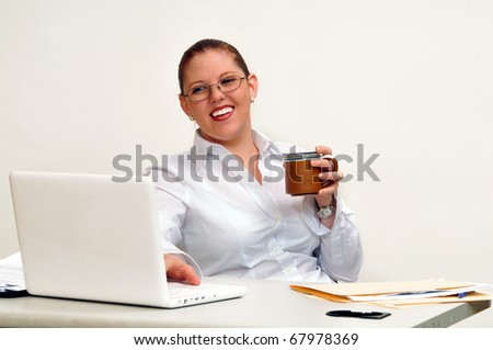 Beautiful, smiling young woman, seated at her desk, leaning back looking at her computer, with coffee cup in her hand