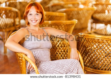 Beautiful smiling young woman sits in armchair against magnificent interior. - stock photo