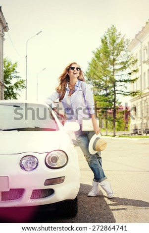 Beautiful smiling young woman stands near her car in the city. - stock photo