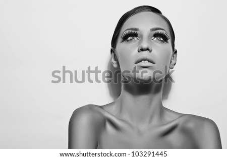 Beautiful smiling young woman stroking her clean beauty face black and white - stock photo