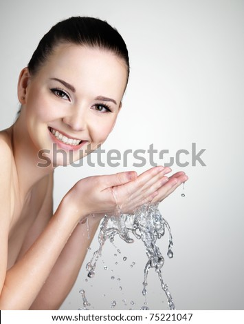 Beautiful smiling young woman washing her face with water - studio shot - stock photo