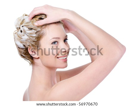 Beautiful smiling young woman washing her hair with shampoo - isolated on white - stock photo