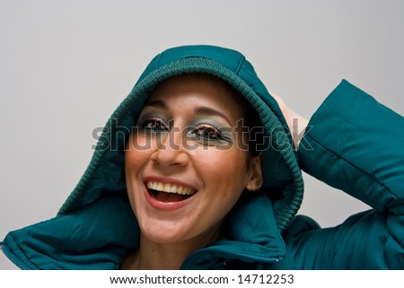 Beautiful smiling young woman wearing a green winter coat with the hood over her head and her hand behind her head - stock photo