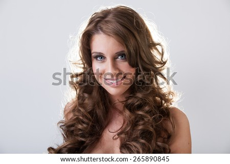 Beautiful smiling young woman with healthy long curly hair - stock photo