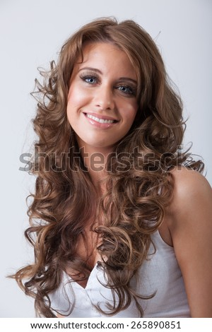 Beautiful smiling young woman with healthy long curly hair