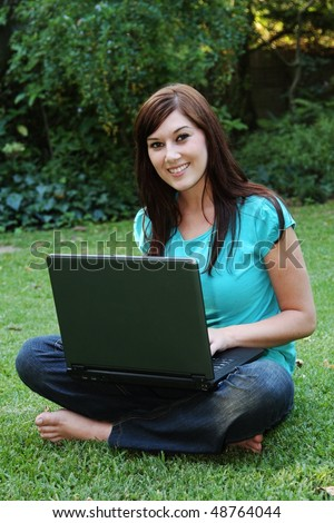 Beautiful smiling young woman with laptop on grass outdoors