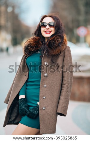 beautiful smiling young woman with long dark hair chic, glamorous sexy brunette girl outdoors, in the street, wearing a green dress and warm coat with fur hood and stylish sunglasses, trendy makeup - stock photo