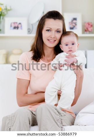Beautiful smiling young woman with newborn baby sitting at home