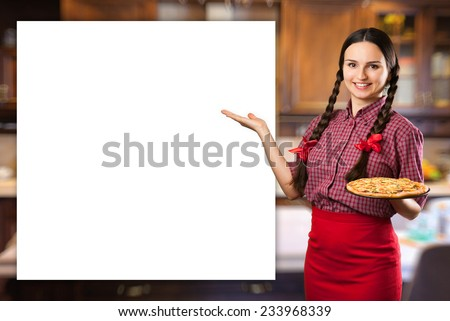 Beautiful smiling young woman with pigtails and red ribbons presenting showing copy space holding a fresh cooked pizza on kitchen background  - stock photo