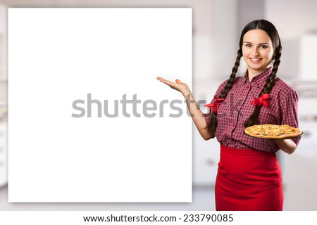 Beautiful smiling young woman with pigtails and red ribbons presenting showing holding a fresh cooked pizza on kitchen background - stock photo