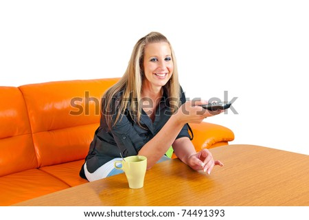 Beautiful smiling young woman with remote control on a sofa in her living room - stock photo