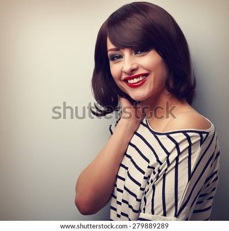 Beautiful smiling young woman with short hair style on blue background. Vintage closeup portrait - stock photo