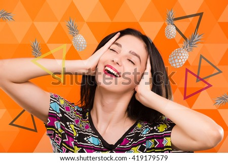 Beautiful smiling young woman, with straight dark hair, wearing on colorful shirt, posing on the orange geometric background with colorful triangles and gray pineapples, in studio, waist up - stock photo