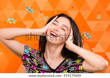 Beautiful smiling young woman, with straight dark hair, wearing on colorful shirt, posing on the orange geometric background with colorful leaves and spots, in studio, waist up - stock photo
