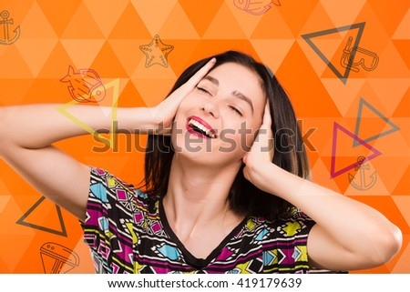 Beautiful smiling young woman, with straight dark hair, wearing on colorful shirt, posing on the orange geometric background with colorful triangles and sea set anchor, starfish, dive mask icons - stock photo