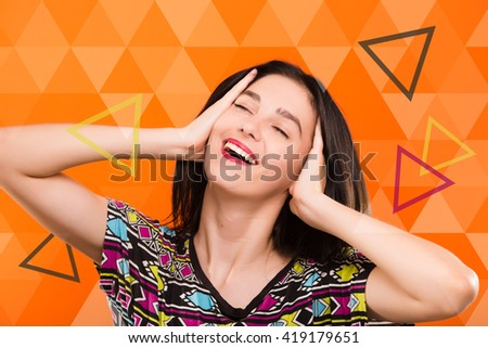 Beautiful smiling young woman, with straight dark hair, wearing on colorful shirt, posing on the orange geometric background with colorful triangles, in studio, waist up - stock photo